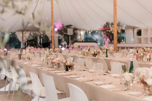 Sfeervol diner aan lange tafels in tent