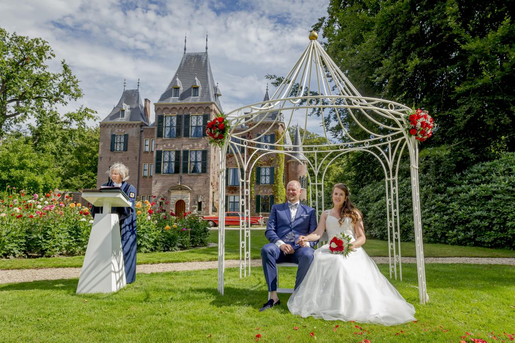 Een huwelijksceremonie in de tuin voor het Kasteel.